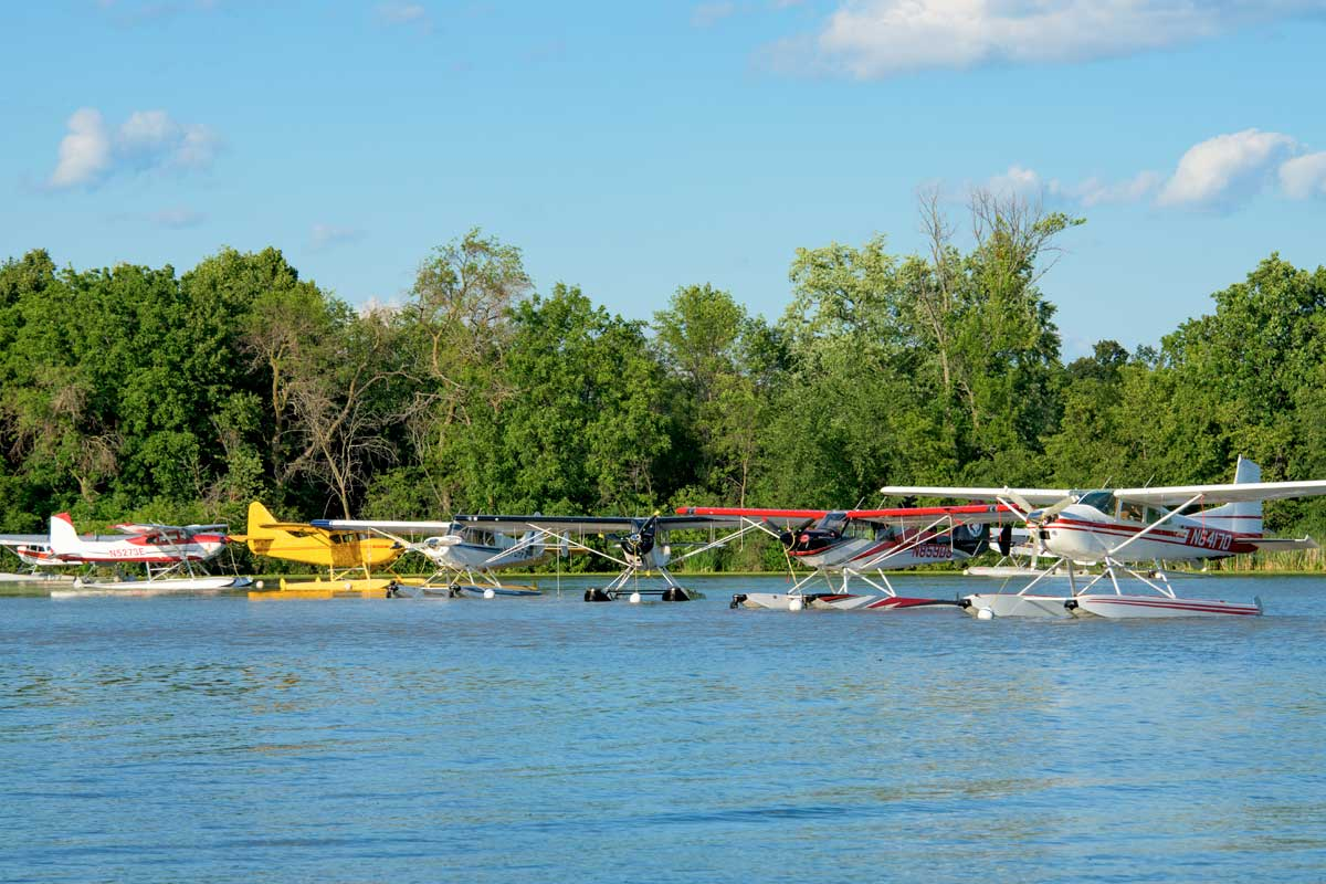 Seaplanes lined up in a row at the lake's edge at Oshkosh