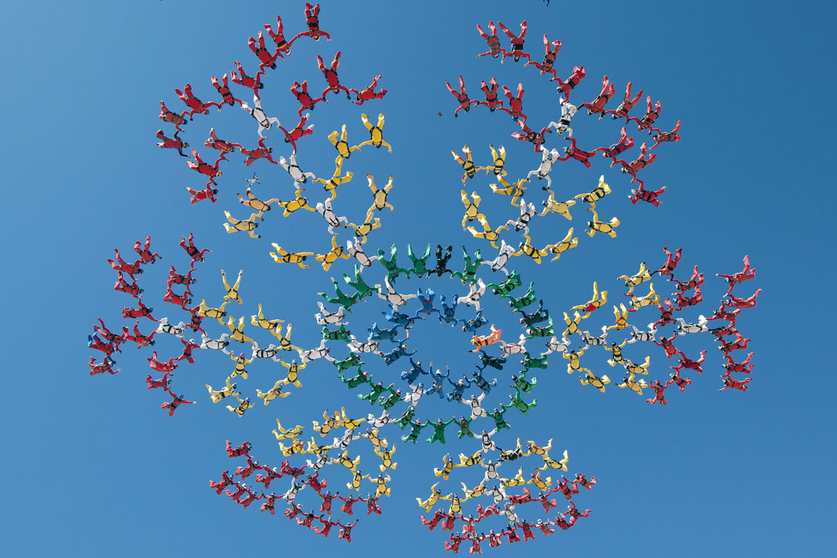 Skydivers in different coloured suits creating a formation in the sky