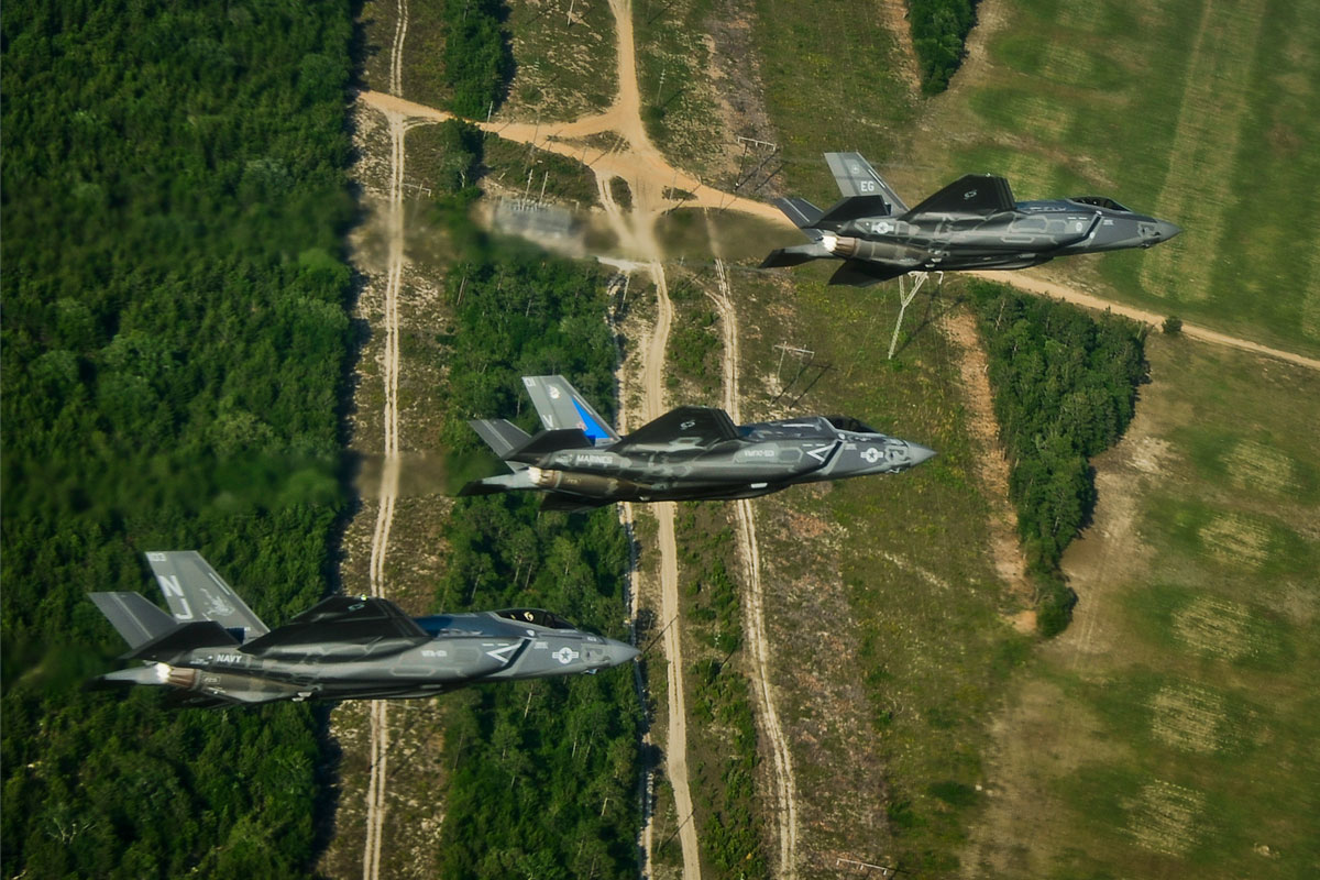 Three US Airforce jets flying a sortie with green forest terrain below them atOshkosh
