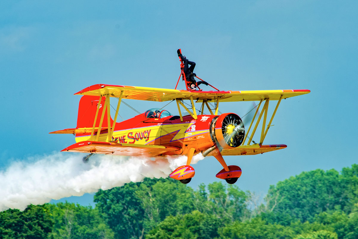 A wing walker performing on a red and yellow biplane emitting a smoke trail