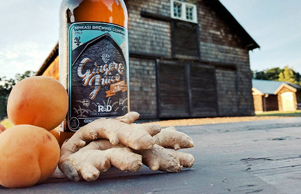A ginger beer bottle with a couple of peaches and fresh ginger on the road in front of the brewery