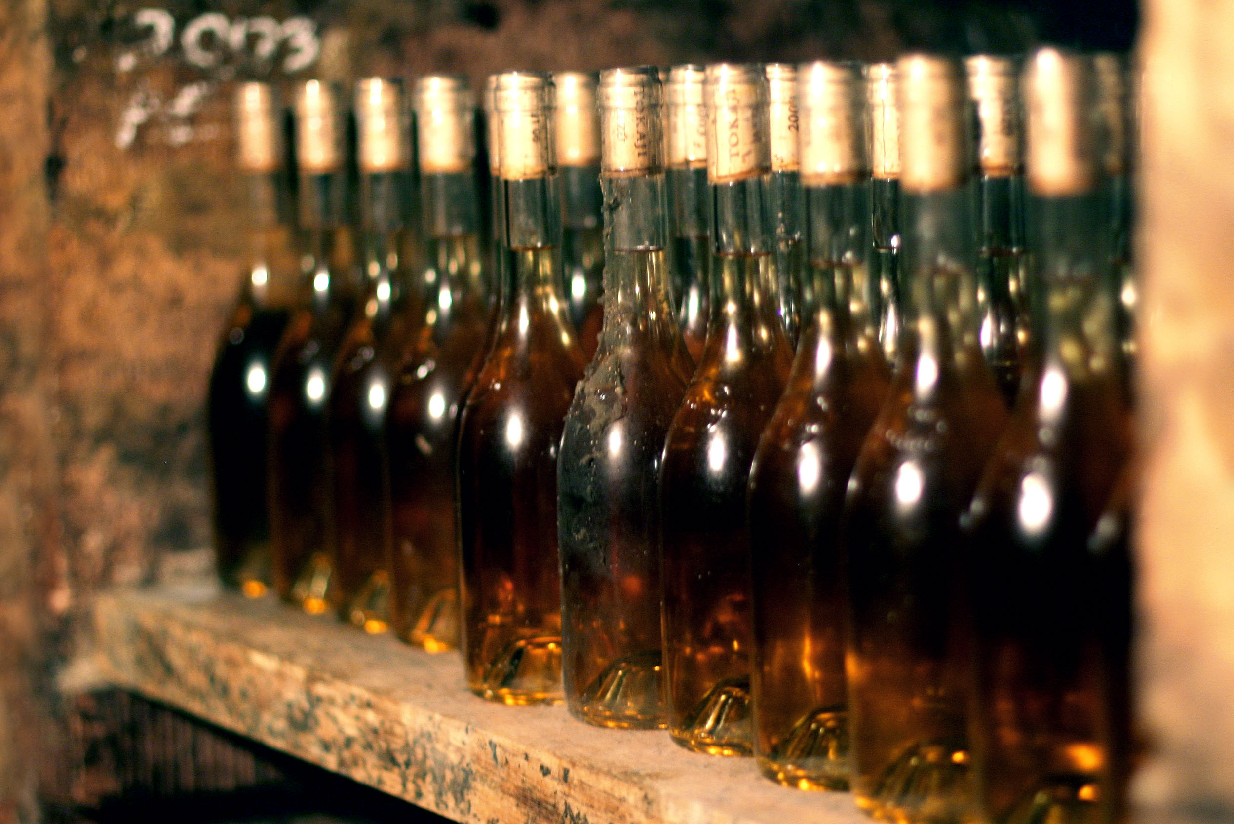 Multiple bottles of tokaj aszú on a wooden shelf
