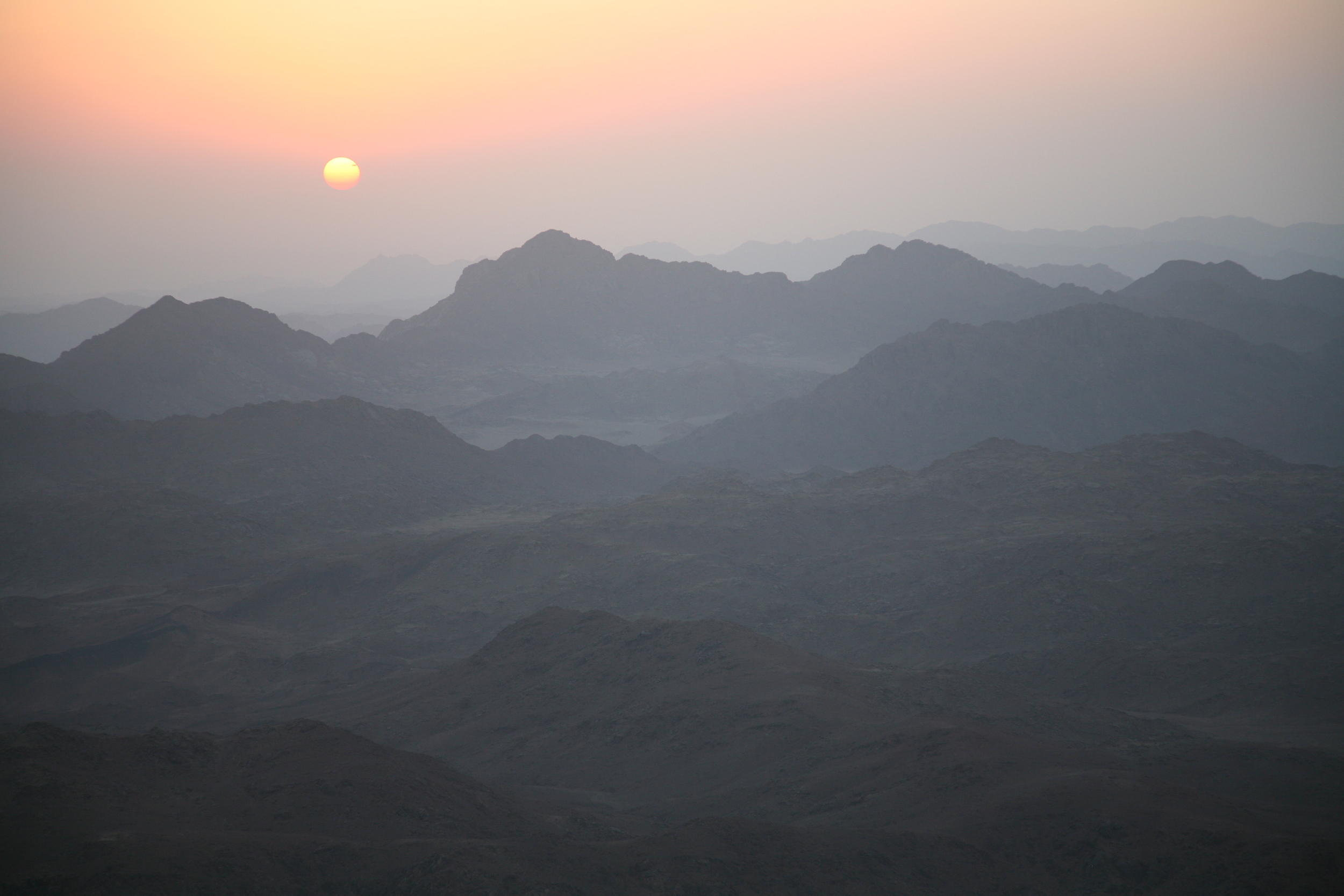 A rising sun over a misty, mountainous landscape at Mt Sinai, Egypt
