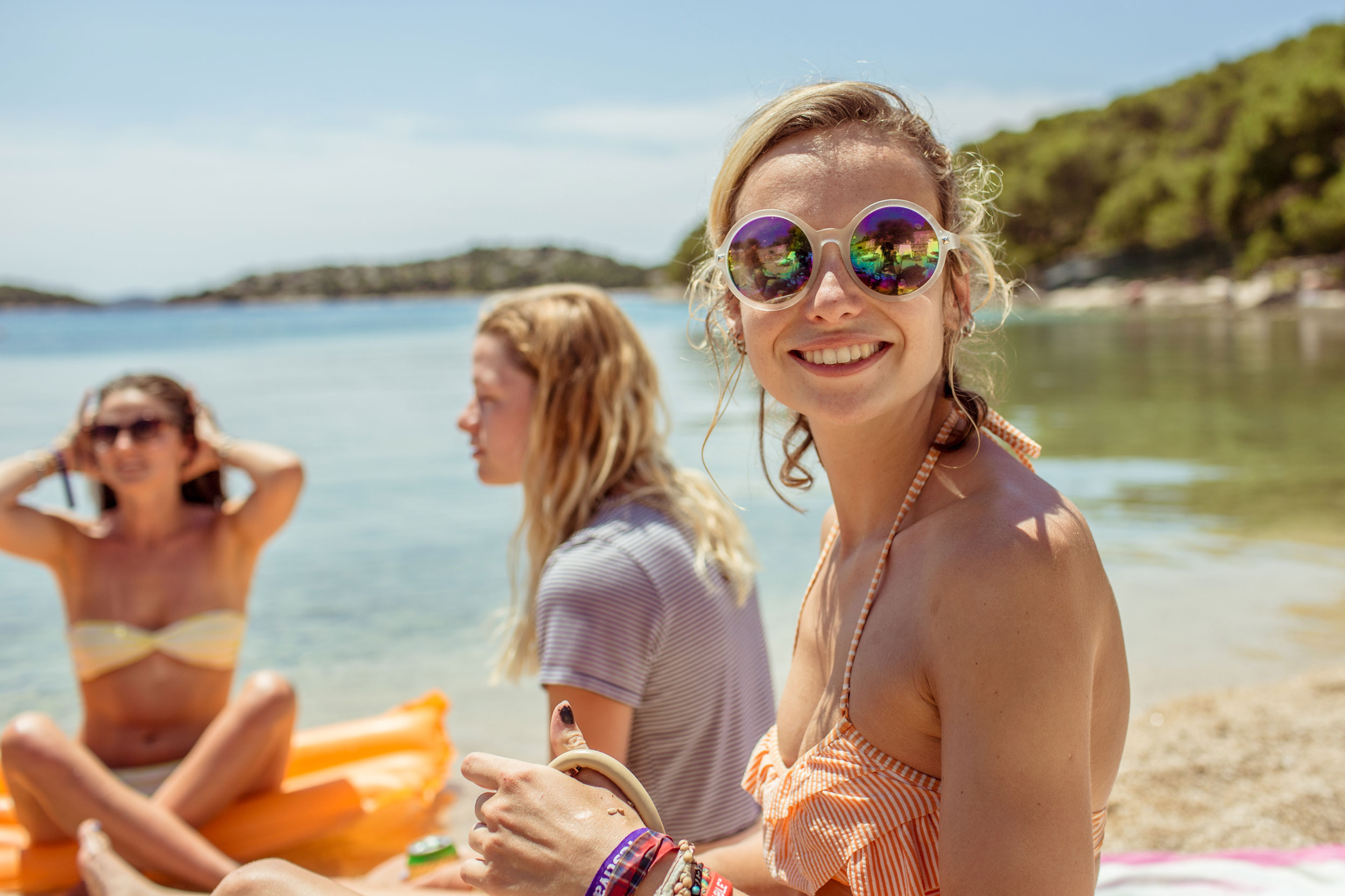 Trio of girls at the beach with the scene reflecting in one of their sunglasses