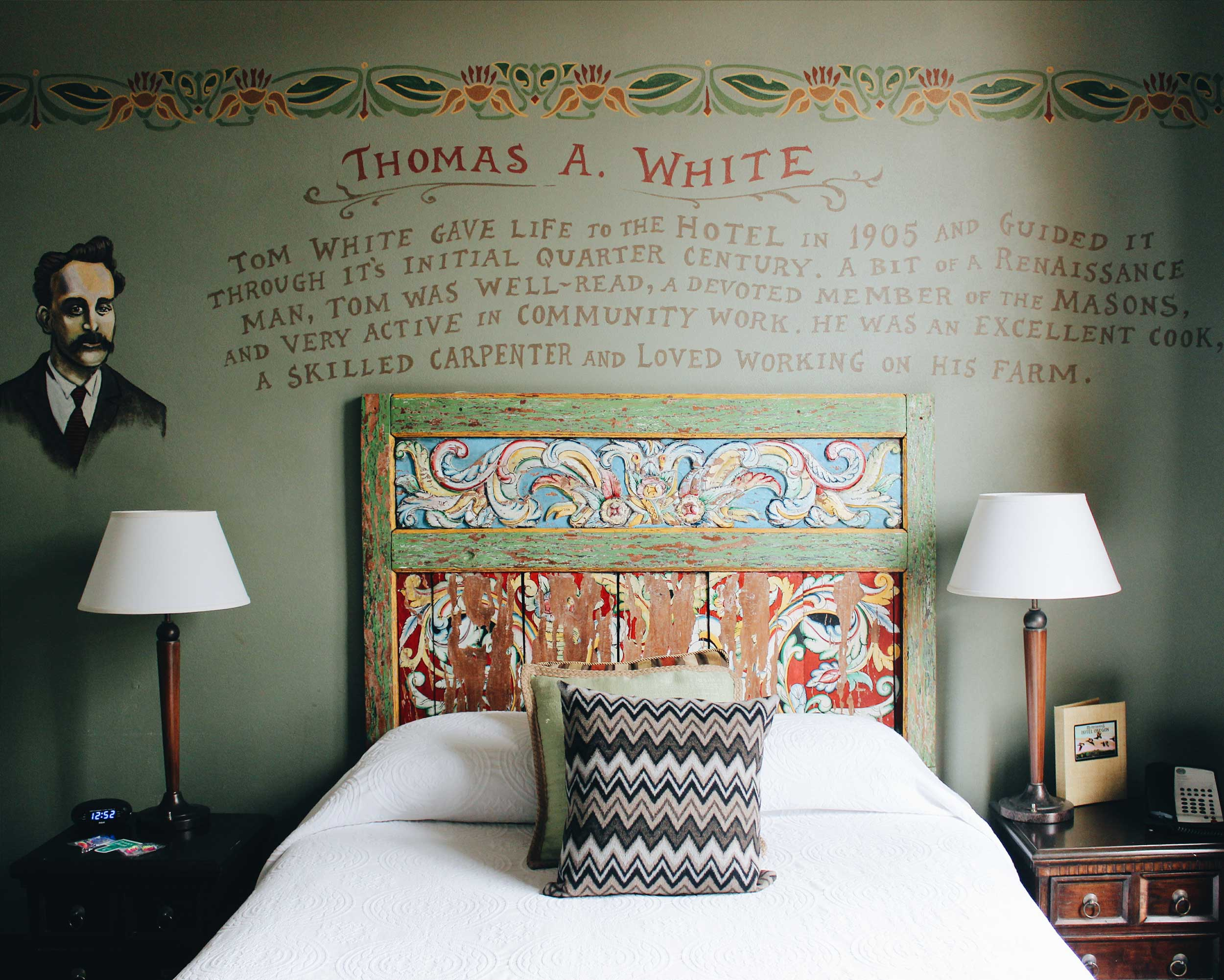 A single bed with an old, battered, painted wooden headboard flanked by side tables with lamps on them at Hotel Oregon