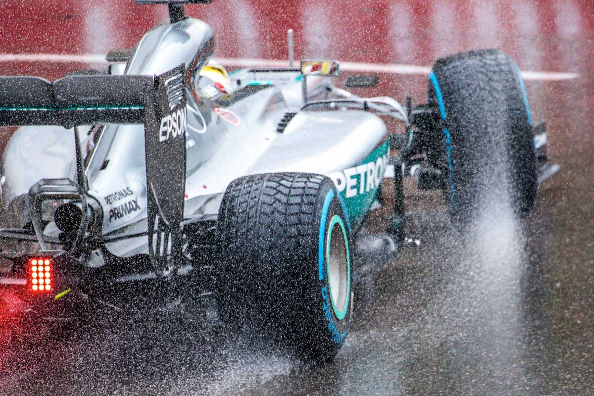 Car in the wet throwing up spray at Monaco
