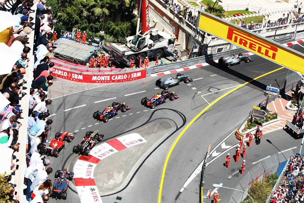 Aerial shot of several F1 cars going round a corner and the crowd above them leaning over to watch, Monaco