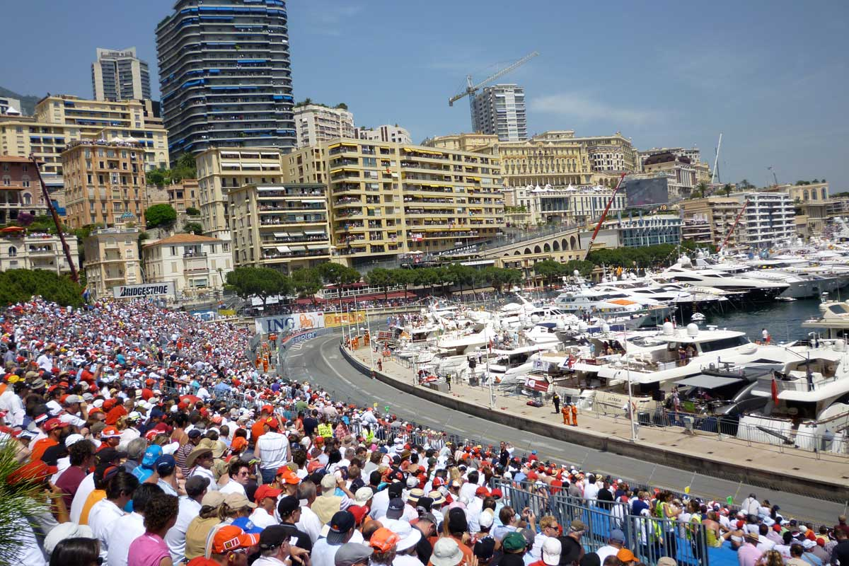 Crowd sitting in stands at a corner of a road going past the harbour and Monaco's buildings in the background