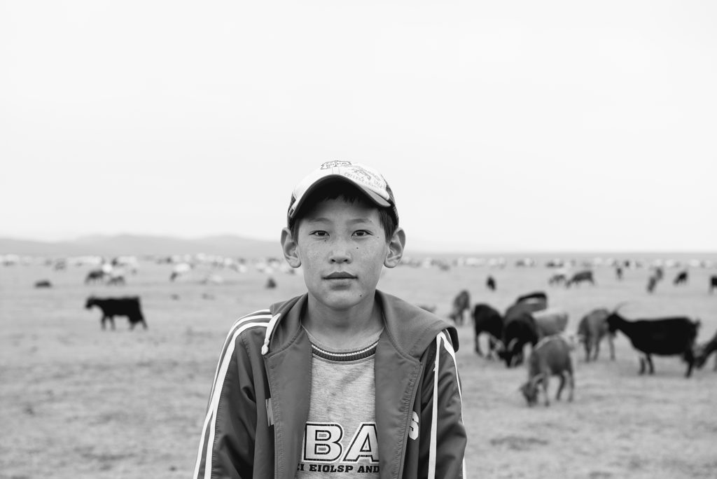 A 10-year-old Mongolian goat herder tending the herd entirely on his own.