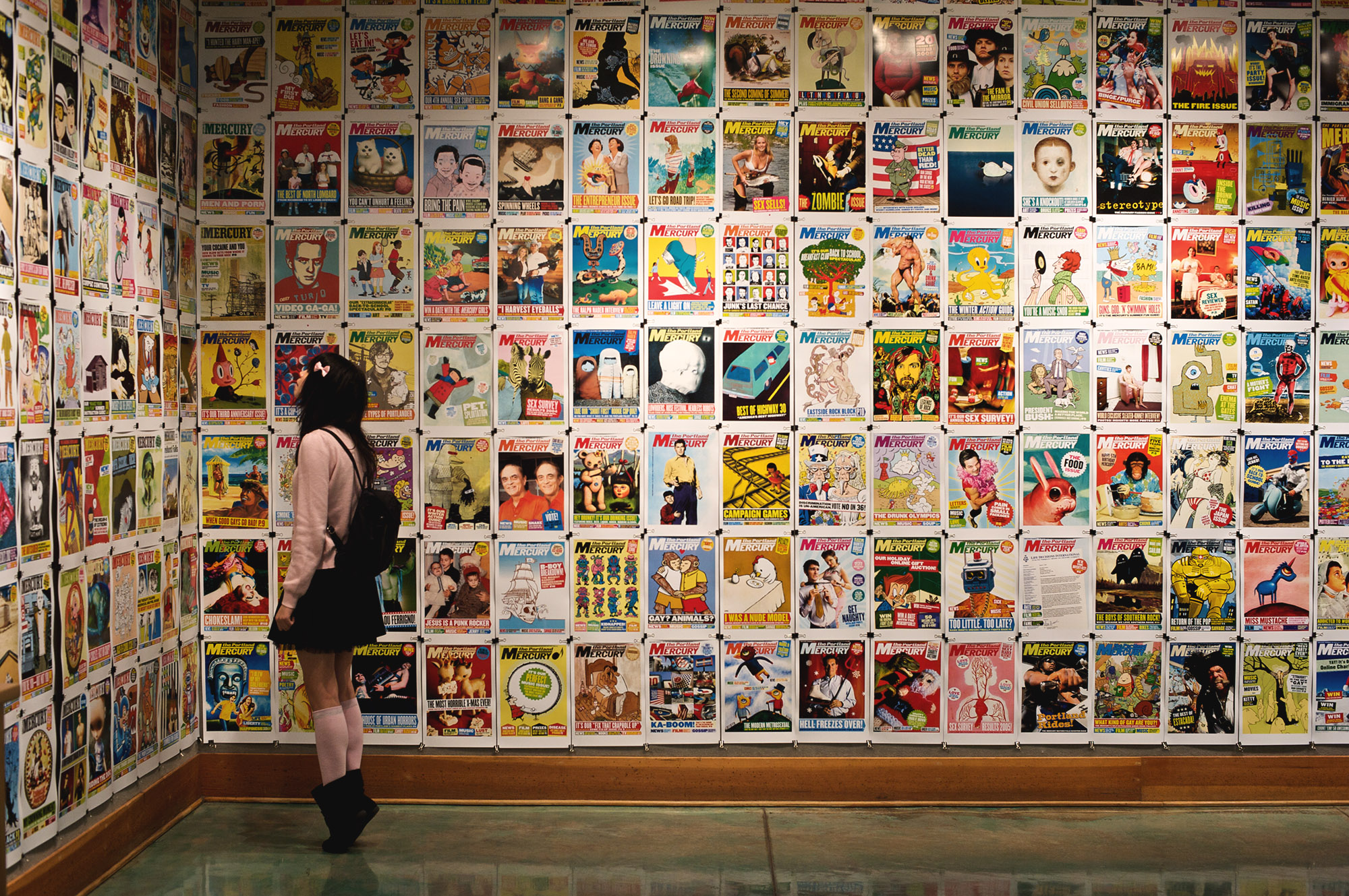 A girl peering intently at walls plastered with Mercury magazine covers