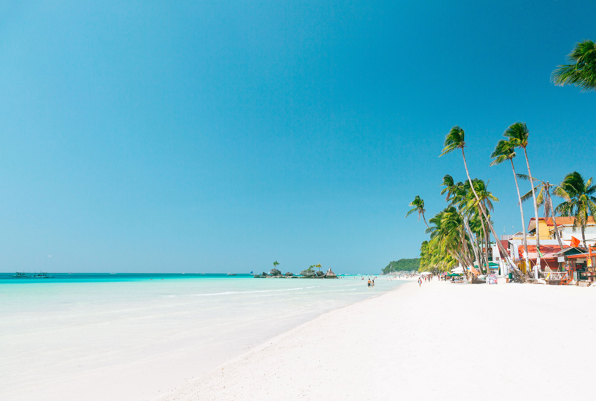 Expanse of white sand and turquoise waters on Boracay Island with buildings and palms further up