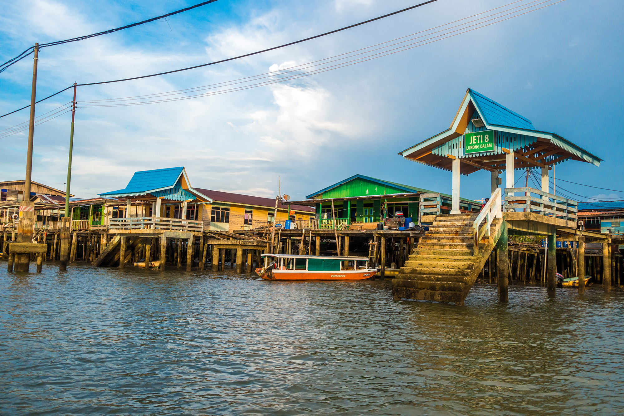 Wooden steps and shacks with coloured roofs on the water at Kampong Ayer