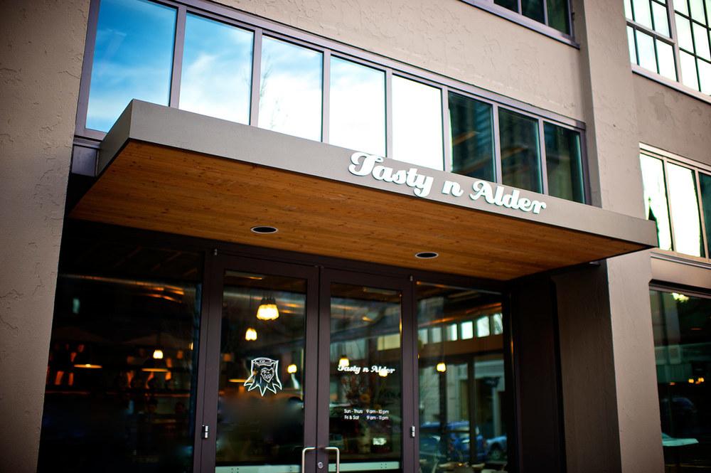The glass swing-doorway to the steakhouse Tasty n Alder, Portland, Oregon