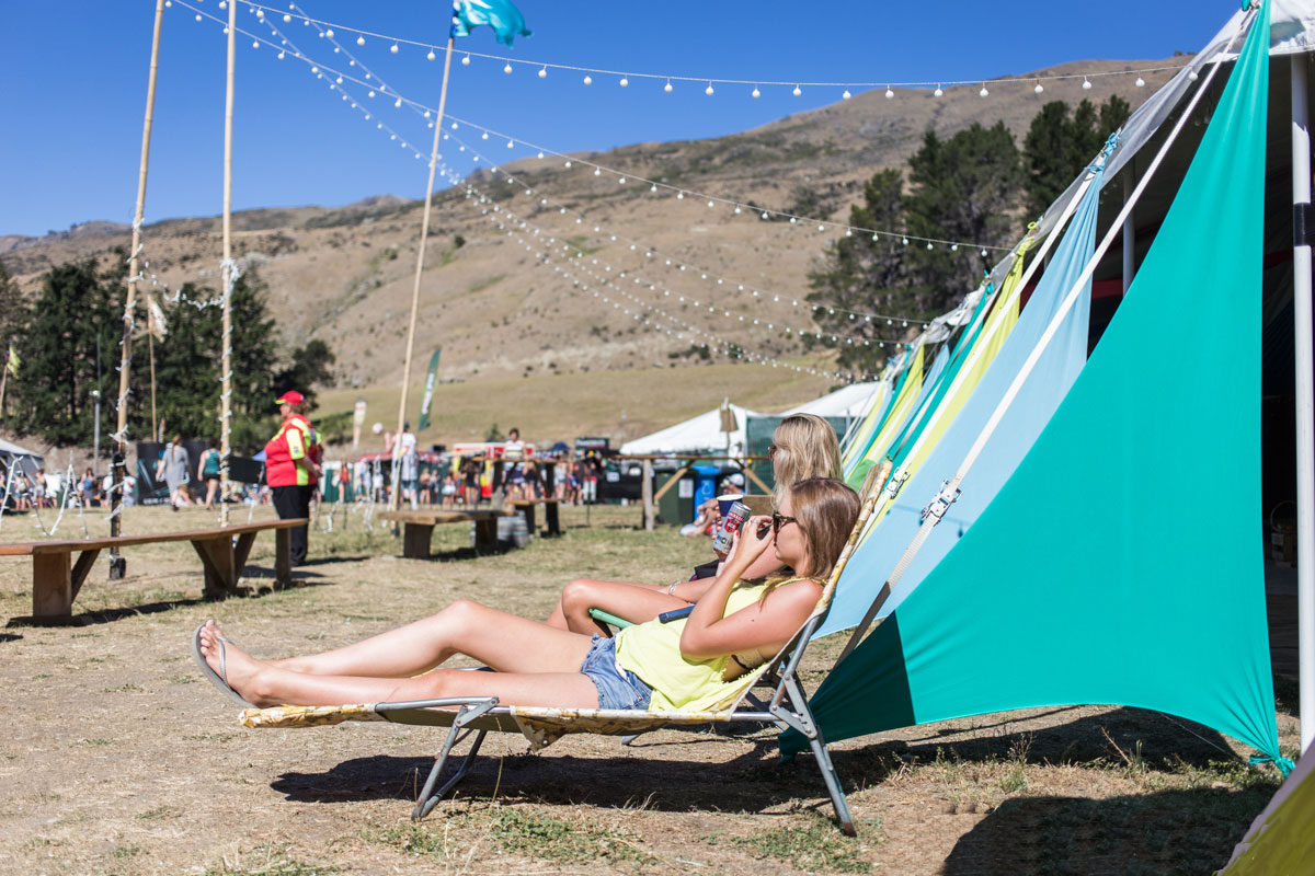 Two girls on loungers outside a line of tents