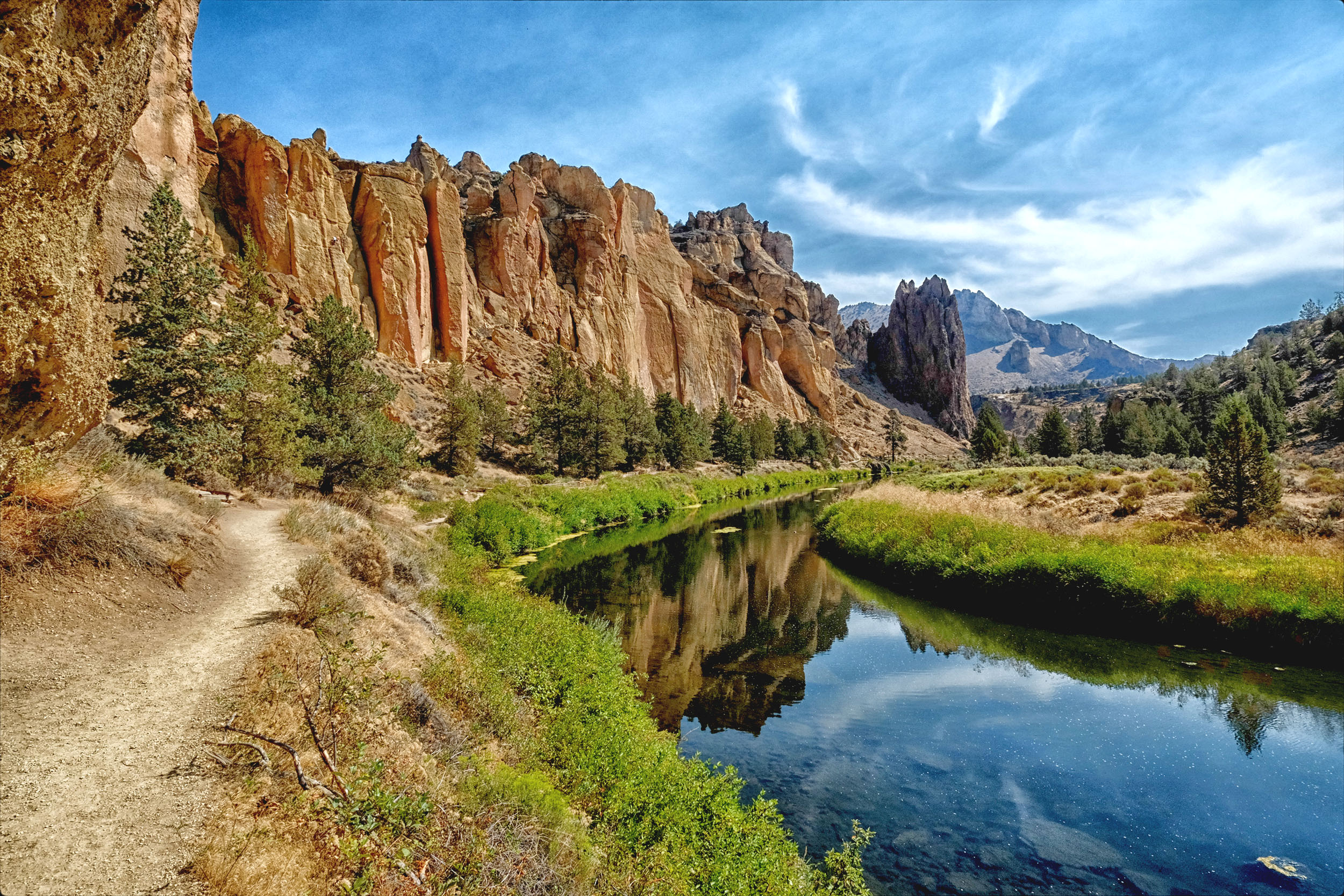 A river cutting through the landscape in front of craggy cliffs at Smith Rock State Park in Bend, Oregon
