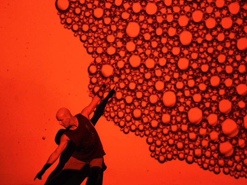 Performer with bubbles on the wall all bathed in blood red light