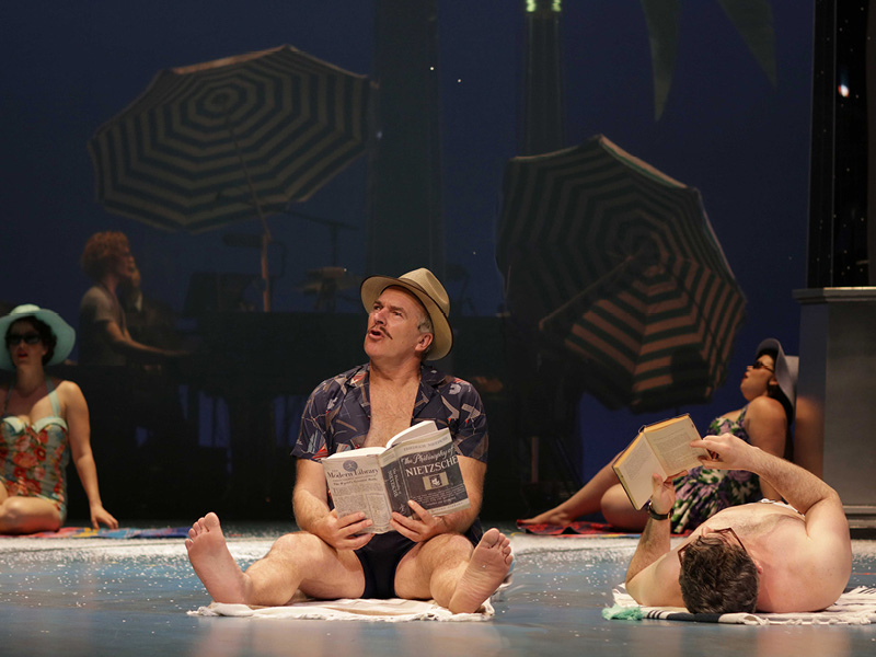 Man with a hat on seated on a towel with a book pretending to be on a beach, Sydney Festival