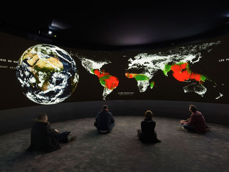Four people seated on the floor gazing at a lighted up, multicoloured giant globe and maps in a dark room, Sydney