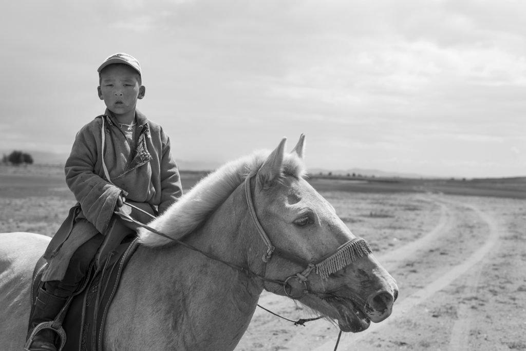 A boy wearing traditional Mongolian dress with a modern baseball cap. He skillfully ascended a steep hill before riding along the ridge towards his grandparents' Ger (yurt).