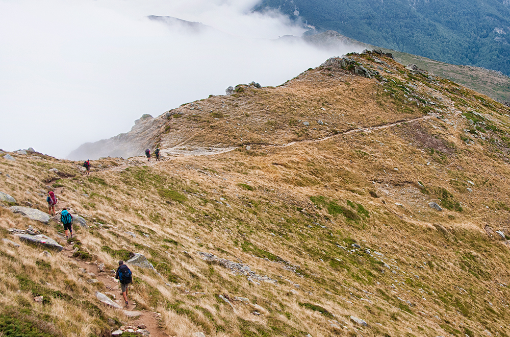 Hikers doing the GR20 walking along a trail on a mountain ridge in Corsica