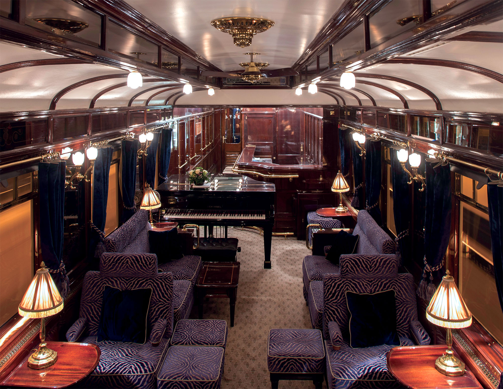 Interior Orient Express train with its couches, piano, side tables and lamps