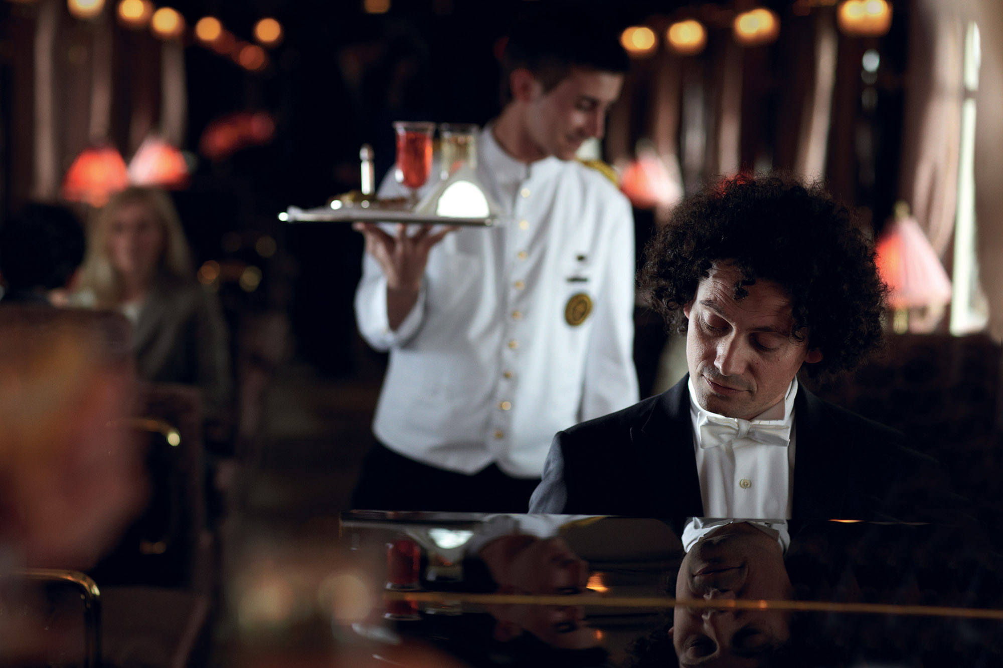 Man sitting at a piano with a waiter carrying a tray with cocktails in the background