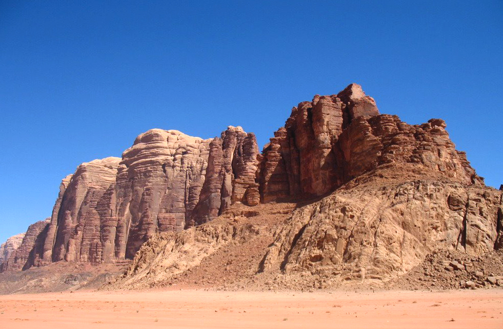 The craggy rock face of Jebel um Ishrin rising from the desert