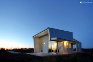 A contemporary villa surrounded by open space, at sunset