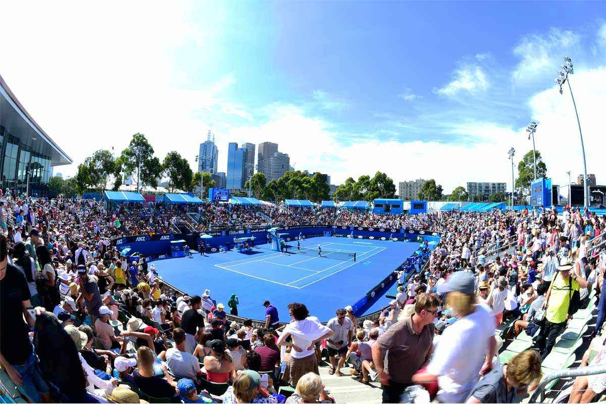 Packed crowds in bright sunshine around a tennis court waiting for the game to start, Australian Open, Melbourne