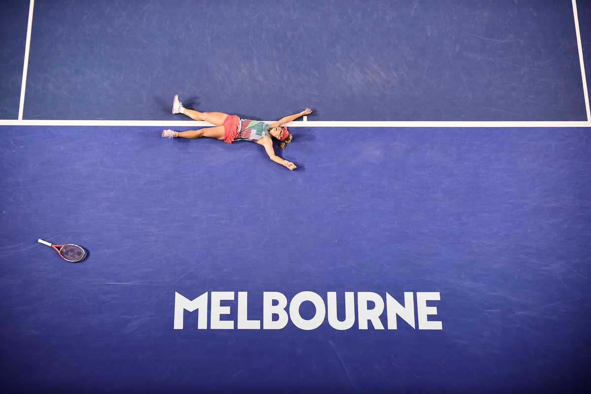 Kerber lying spreadeagled on the blue tennis court next to her racket, in relief after her game