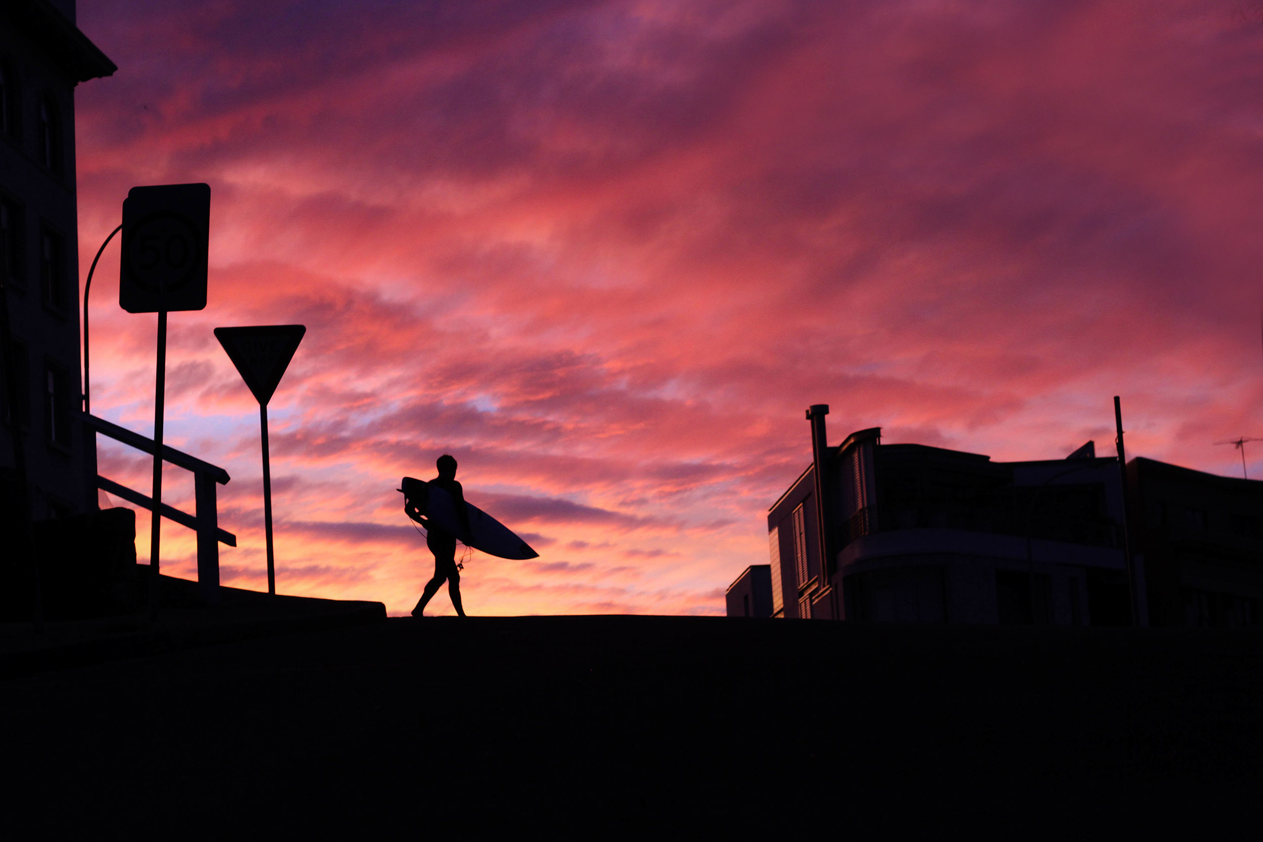 Surfer holding surfboard silhouetted against fiery red sunset sky walking across the pier in Bondi Beach
