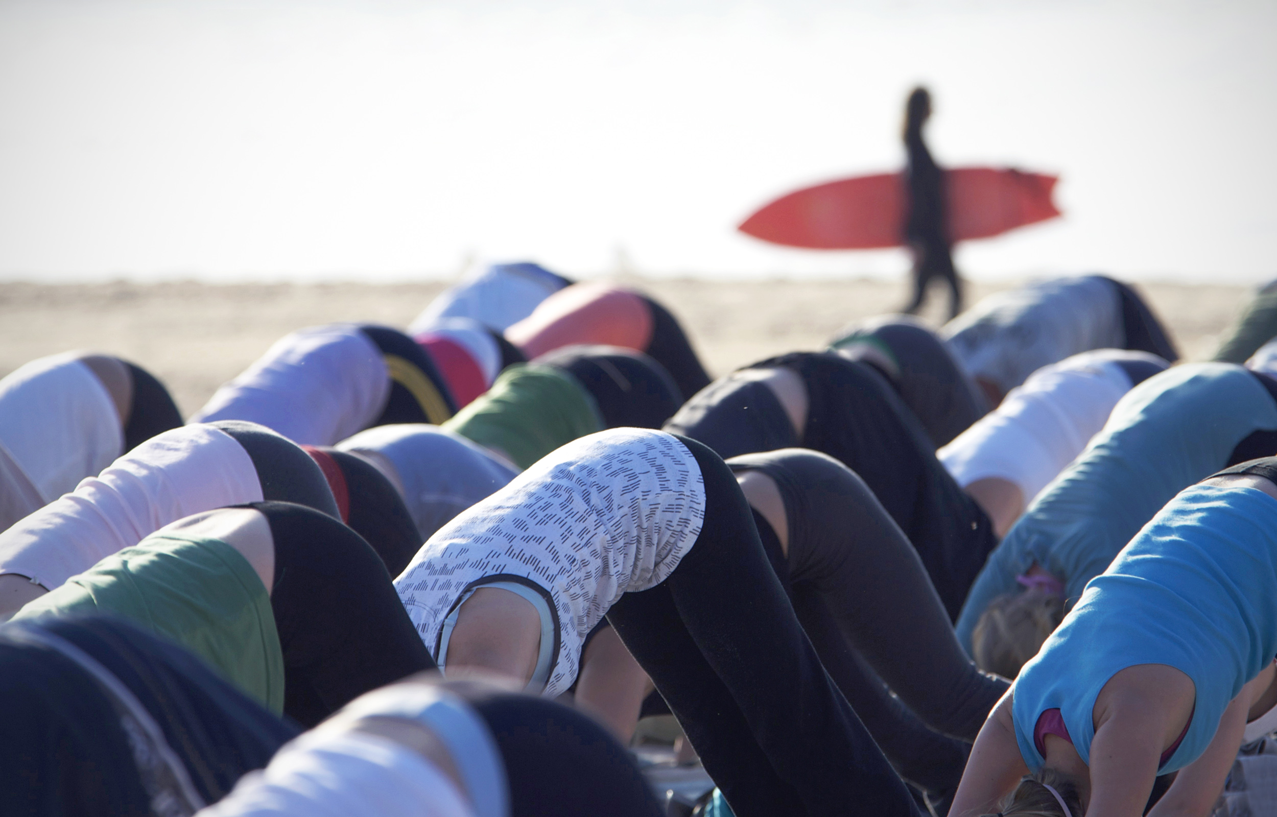 Group of ladies doing downward dog yoga pose on the beach, surfer in background, Bondi Beach, Sydney