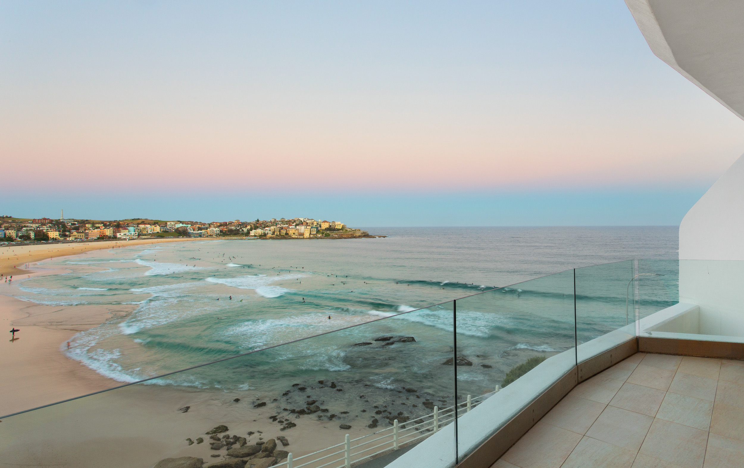 View of Bondi Beach at sunset taken from above with an orange-blue hazy sky