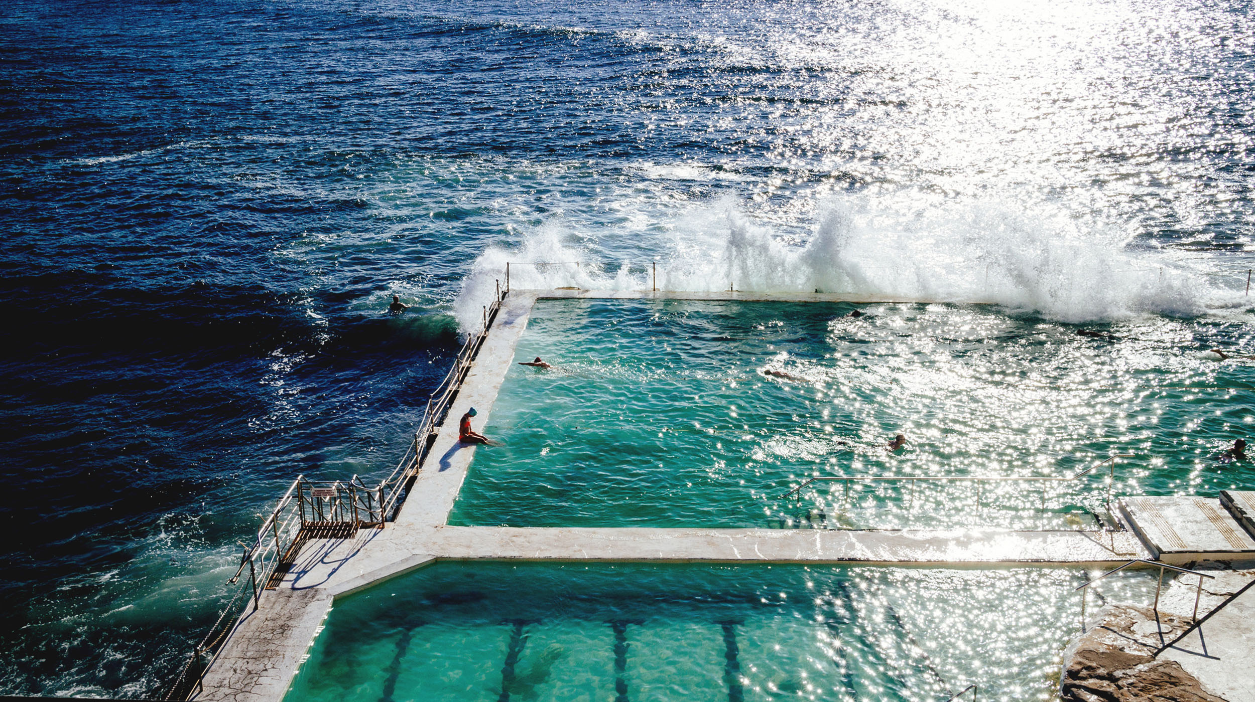Sunny oceanside pools with waves crashing into the side and a person diving in