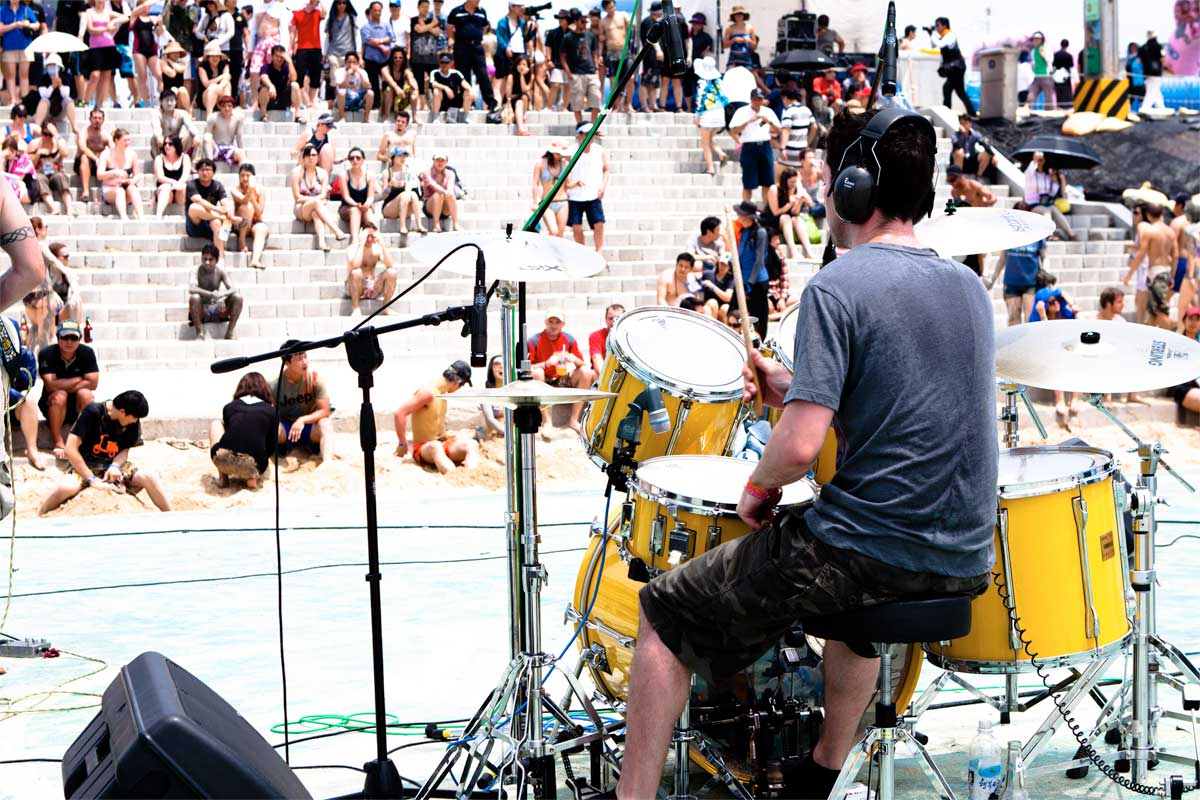man playing on a yellow drumset to the crowd sitting on the steps in front of him