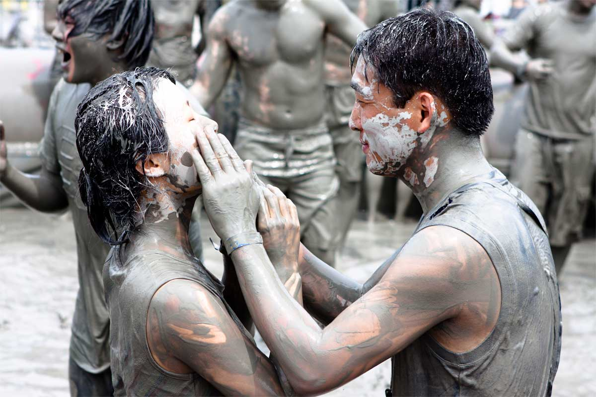 A couple smearing mud on each others' faces at Boryeoung Mud Festival