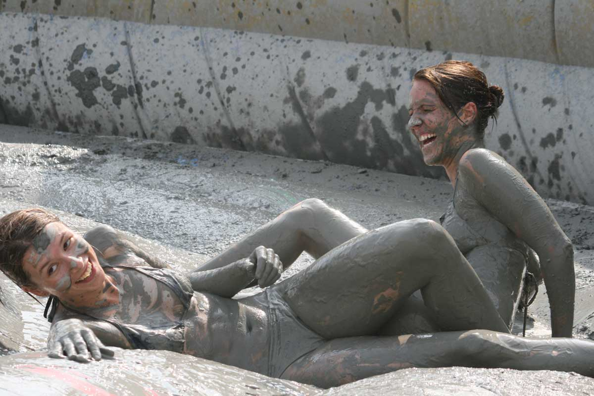 Two girls laughing away lying in the mud pool at Boryeoung