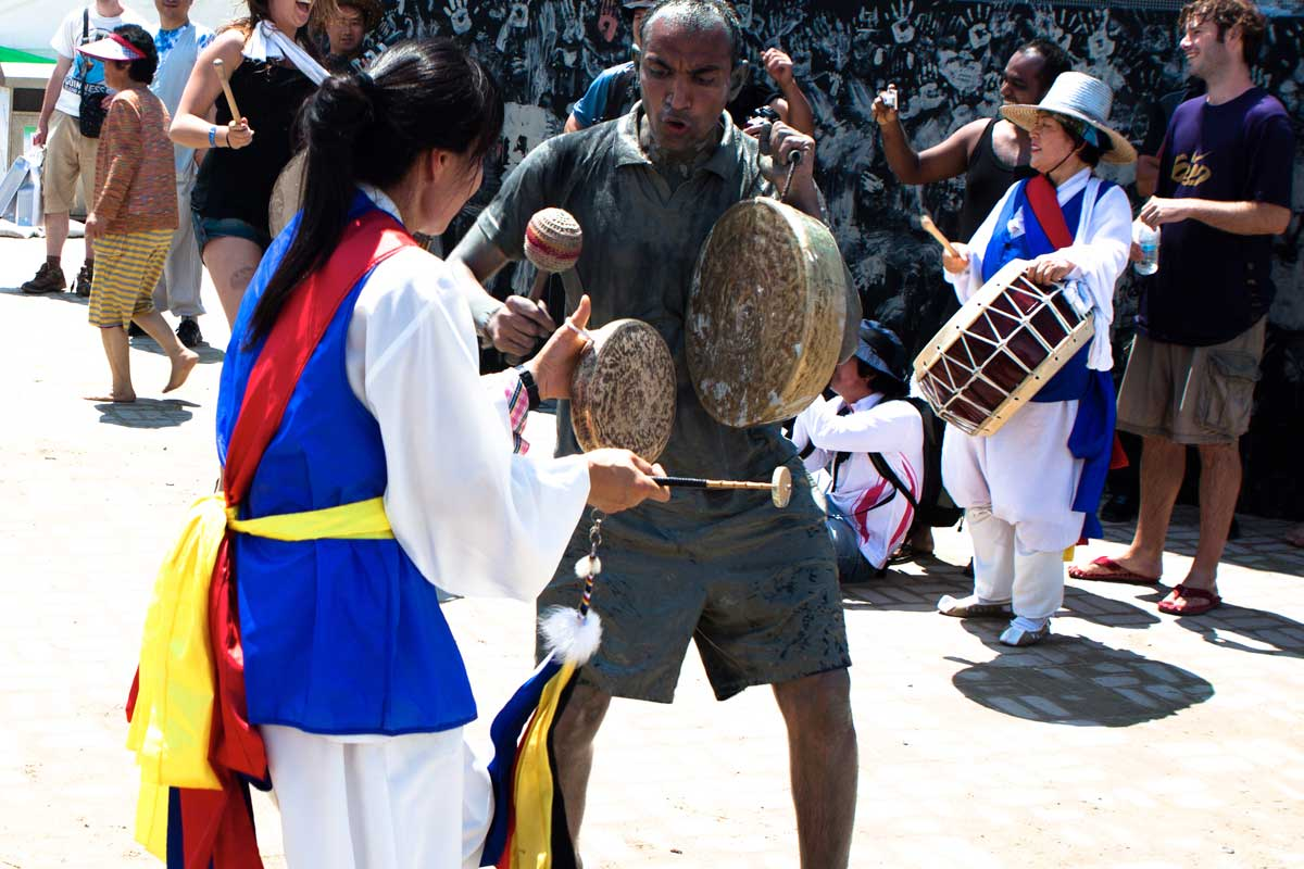 Girl in tarditional clothes and an excited man playing gongs