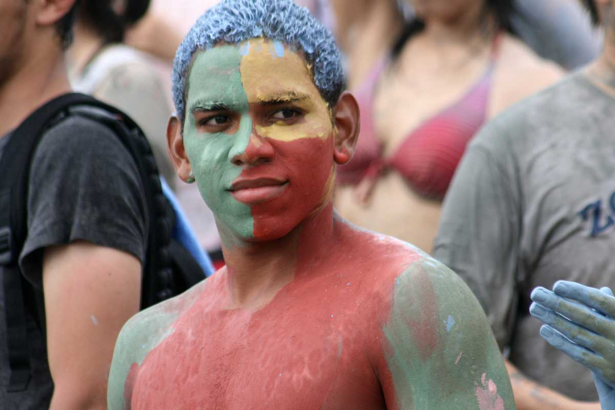 Man with his face and body painted in many colours at the mud festival