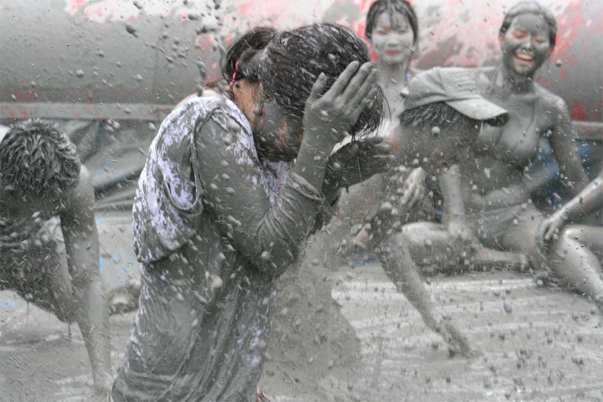 Girl shielding her face from mud splatter