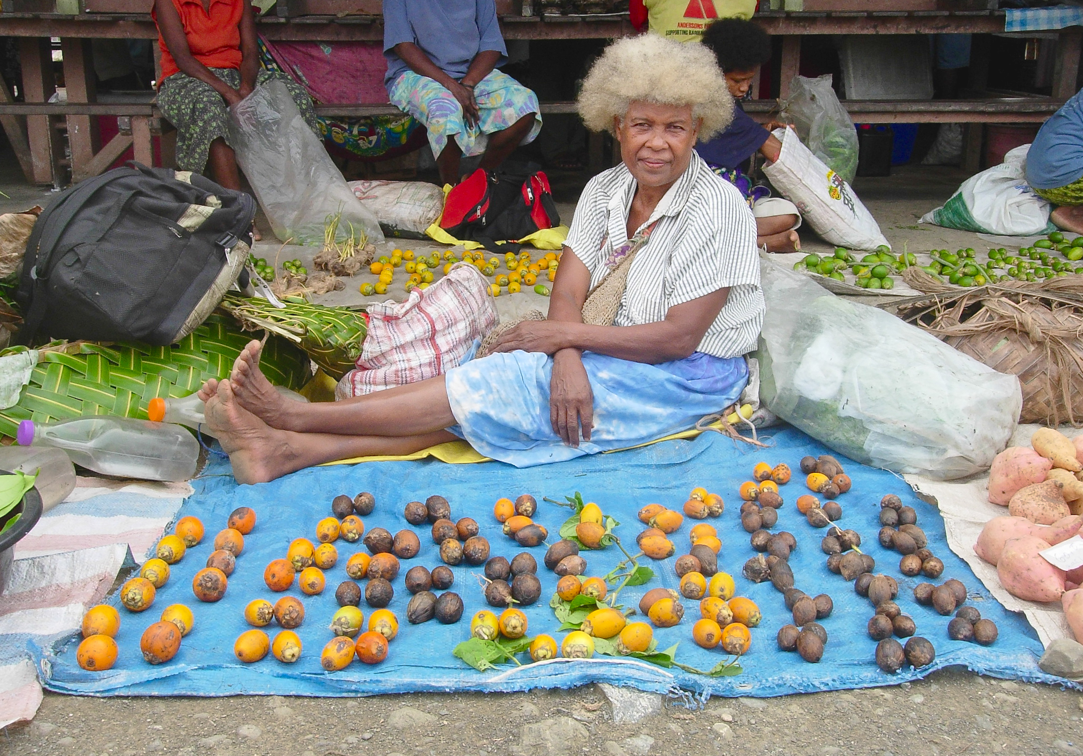 Elderly lady sitting on a blue tarpaulin with betel nuts spread in front of her
