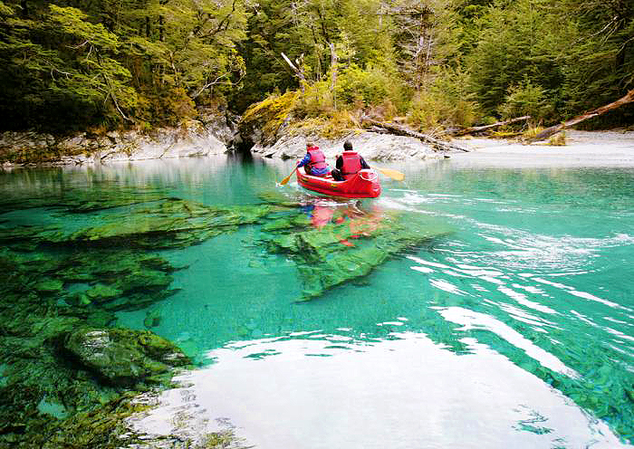 Two men in a red kayak rowing through incredibly clear blue-green water seeing down to the rocks and riverbed