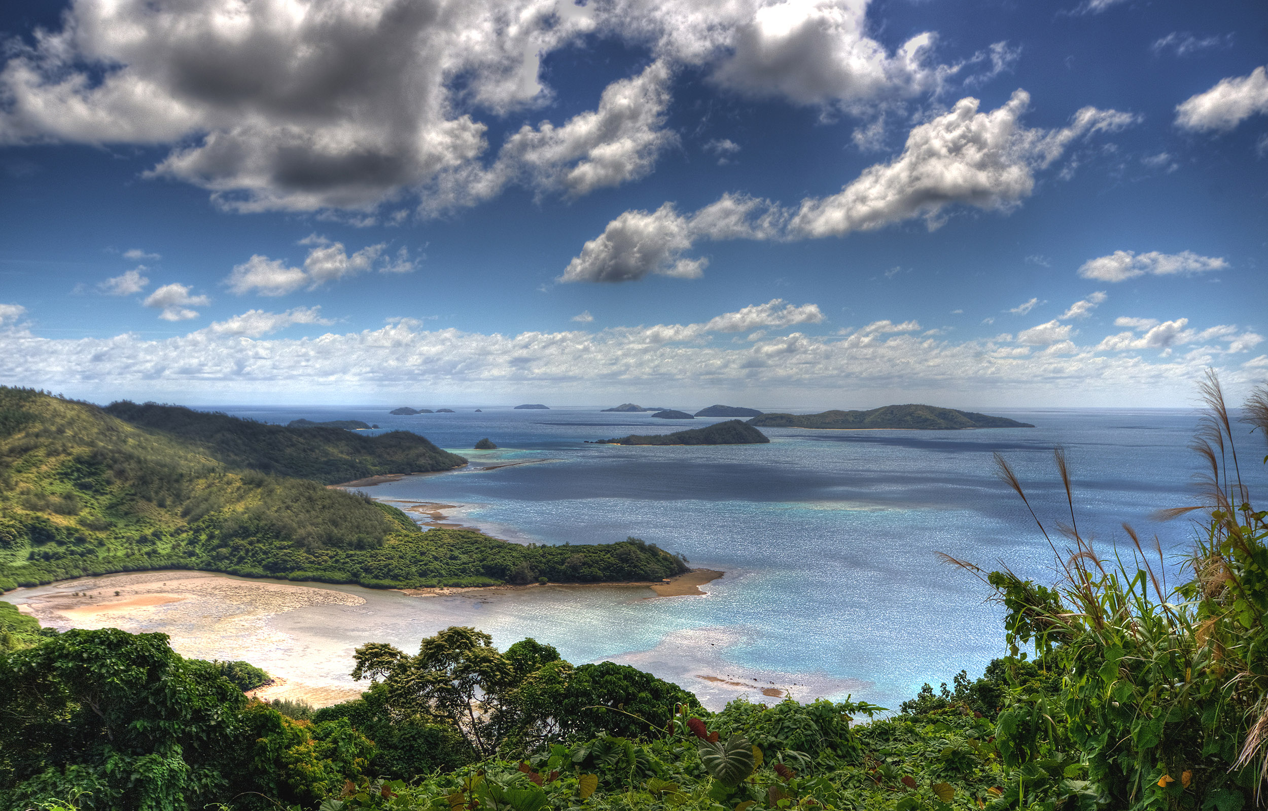 Looking down onto a couple of bays and outlying islands with an overcast sky in Fiji