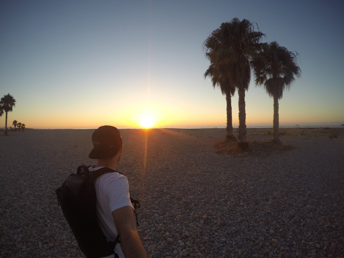 Sunset over a beach in Valencia with trees silhouetted and a man wearing a backpack in front