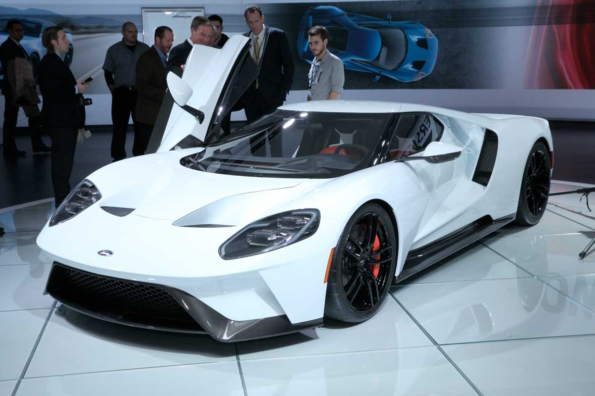People admiring a white Ford supercar with one gullwing door open at NAIAS, Detroit