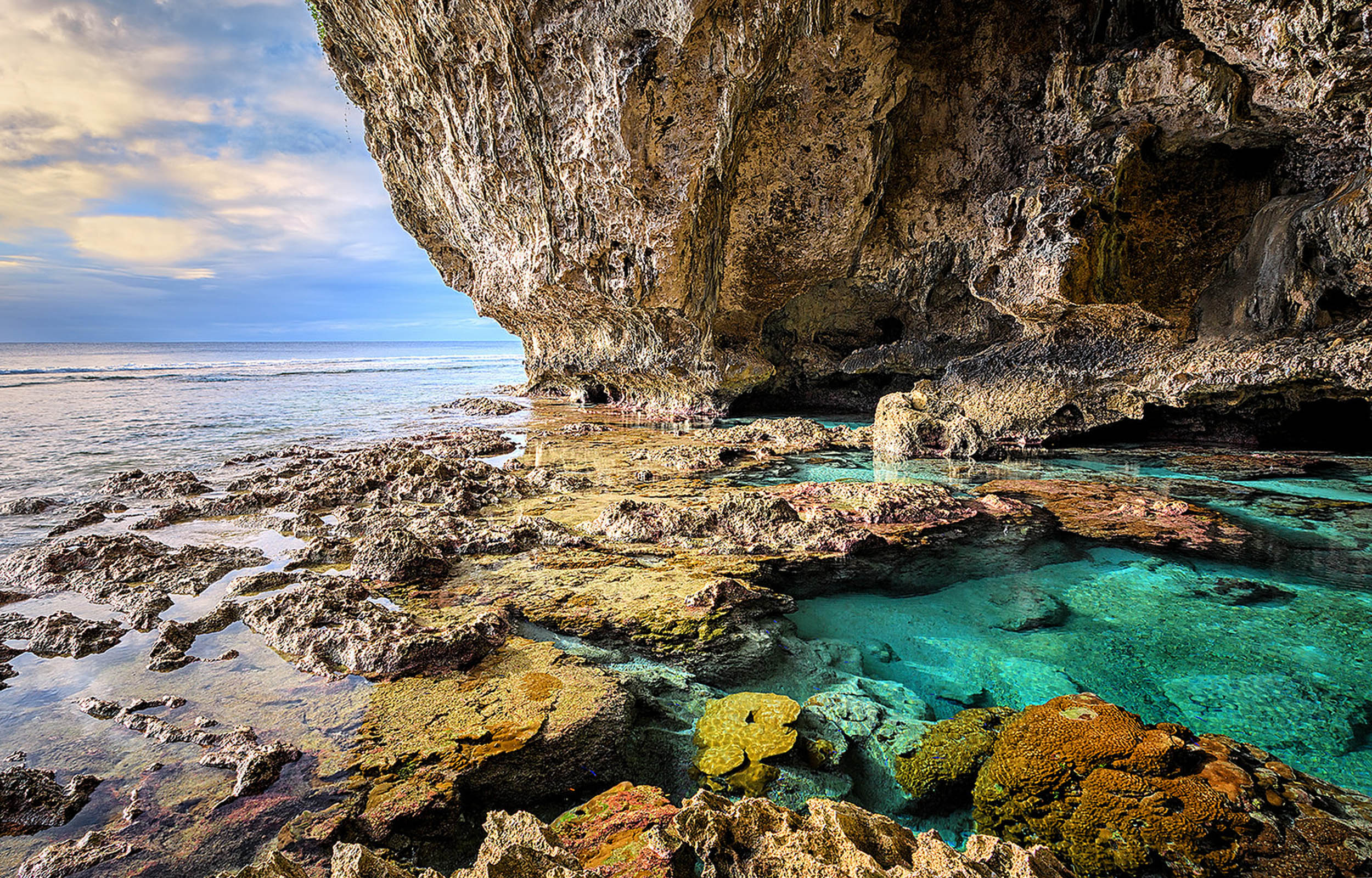 Cave wall and rocky floor with coral in limpid blue water pools facing out to the ocean at Niue