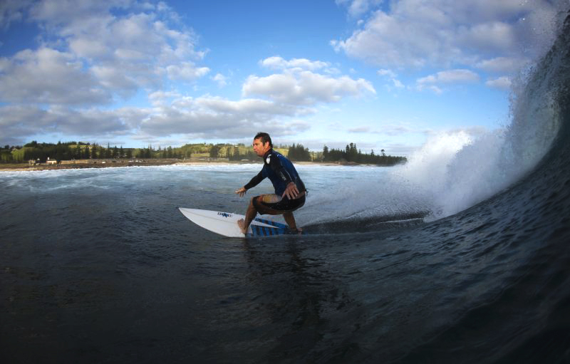 Surfer on the water with a wave curling behind him and Kingston beach in the distance, Norfolk Island