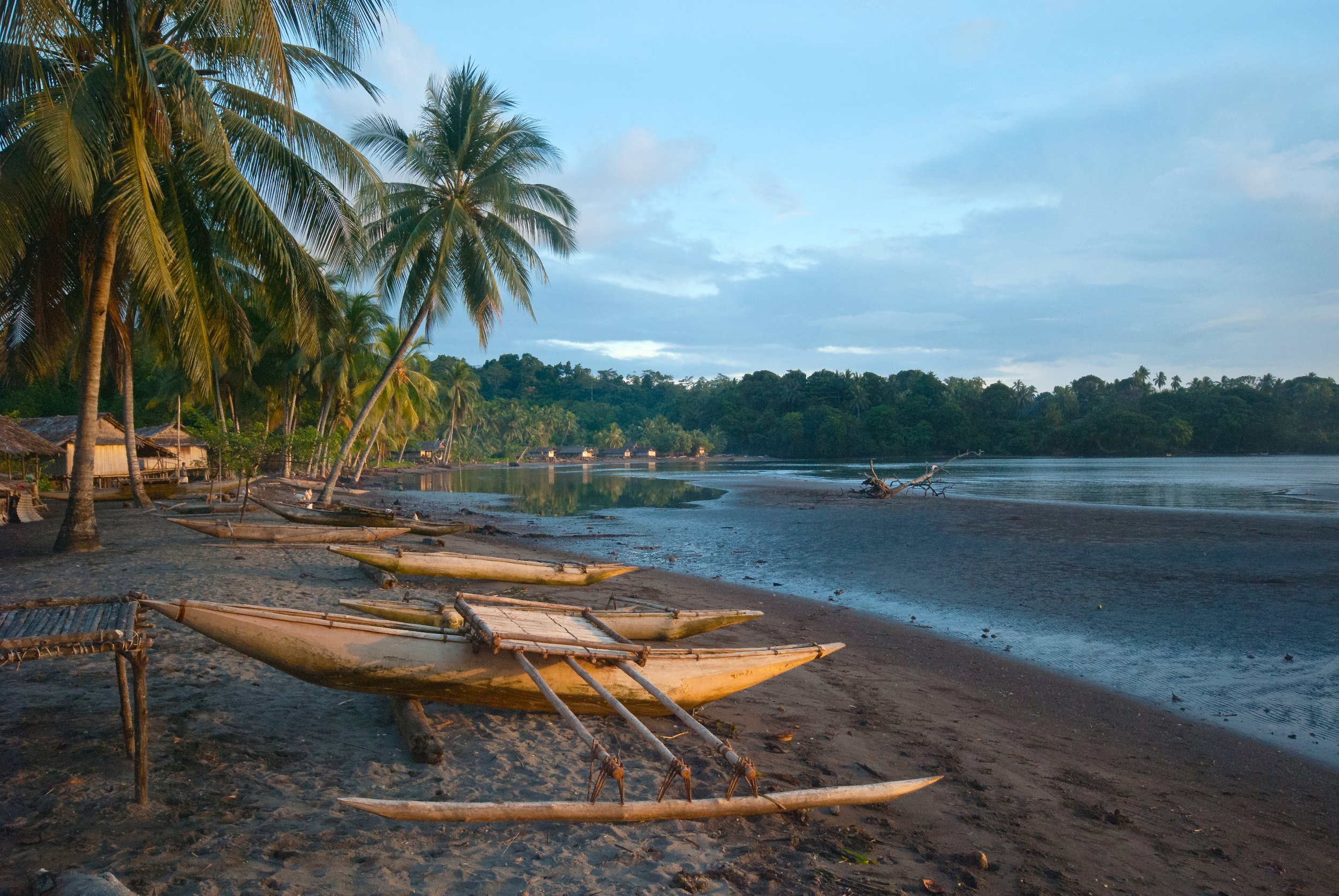 Traditional wooden canoes on the beach at dusk and low-tide, Papua New Guinea