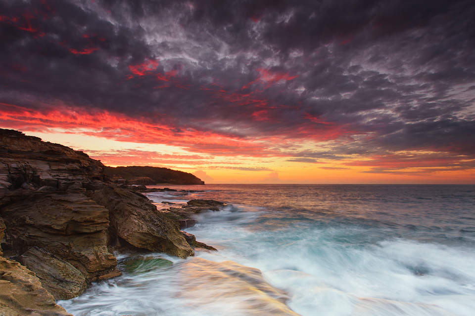 A vibrant orange sunset above the rocks and sea foam of Putty Beach, Australia