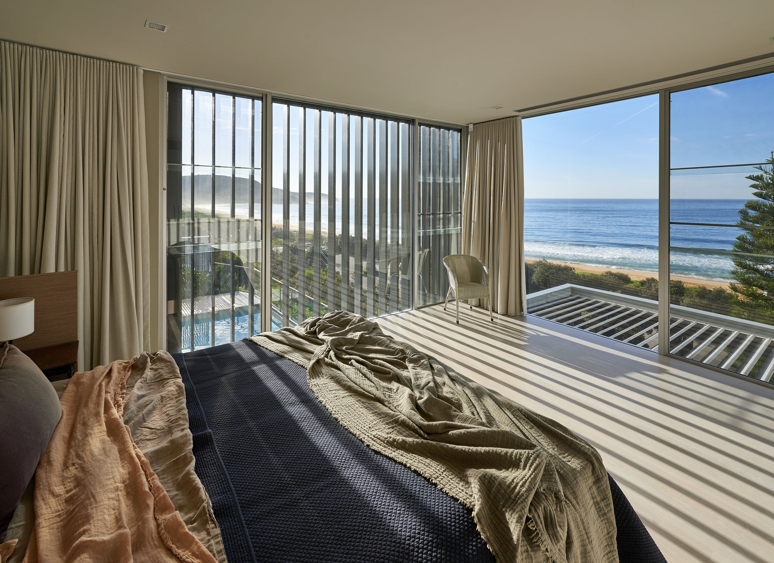 A view of the bed and out to the sea from the master suite's glass doors and walls at Killcare Beach House